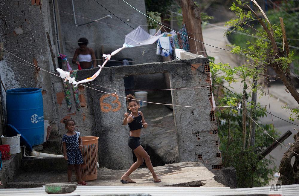 A young watches as her homemade kite takes flight in the Complexo da Penha slum's Chatuba neighborhood, in Rio de Janeiro, Brazil, Aug. 22, 2018. (AP Photo/Silvia Izquierdo)