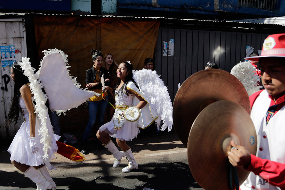 Members of Paraguay's Bolivian community perform in costume during a street procession in honor of Our Lady of Urkupina, in Asuncion, Paraguay, Aug. 26, 2018. (AP Photo/Jorge Saenz)
