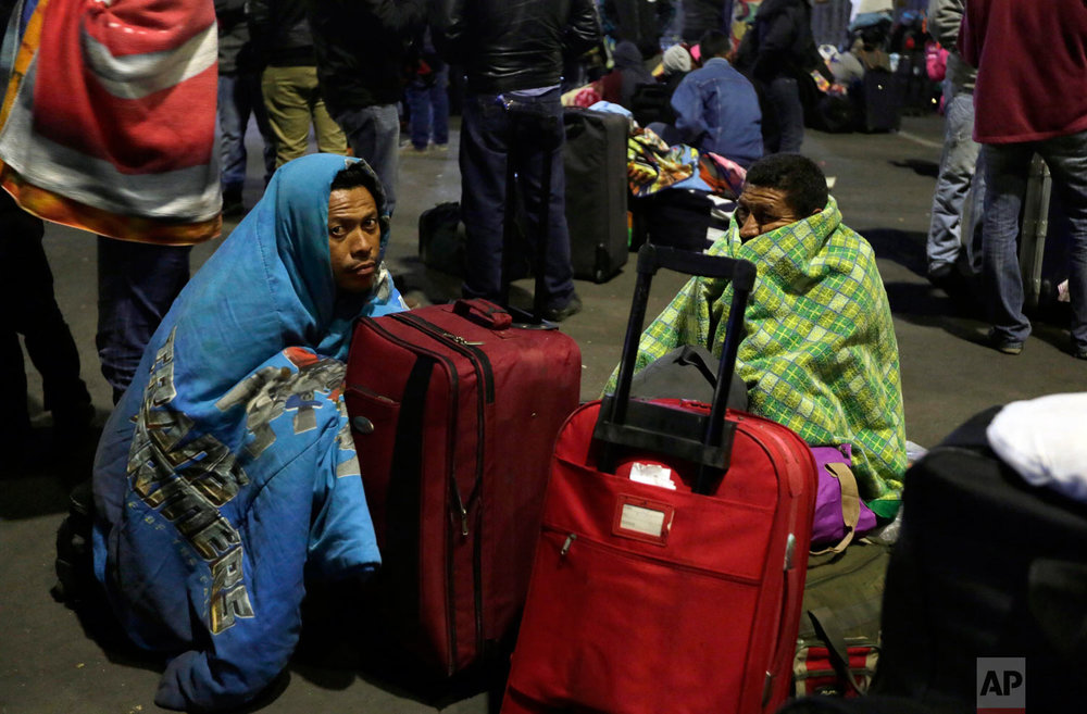 Venezuelan migrants wait for a decision from immigration authorities that allows them to enter Ecuador without a passport after the deadline passed on new regulations that demand passports from migrants, in Rumichaca, Ecuador, Aug. 18, 2018. The United Nations estimates 2.3 million Venezuelans have fled since 2014, the majority of them going to Colombia or Peru.(AP Photo/Dolores Ochoa)