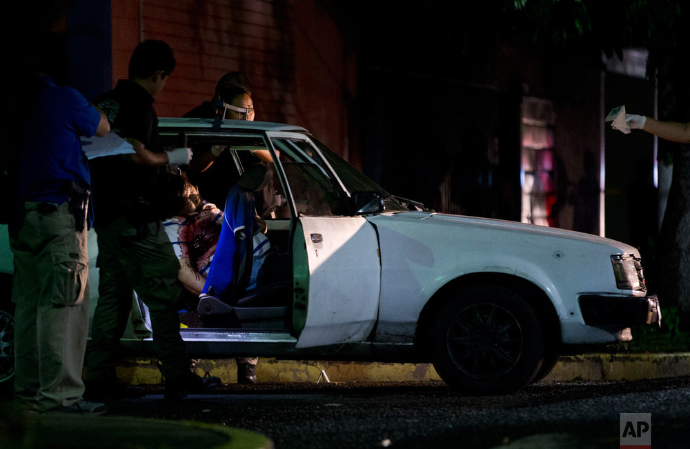 Forensic investigators examine the crime scene where a man was executed while driving his car, in San Salvador, El Salvador, Aug. 20, 2018. El Salvador is considered one of the world's most violent countries, and authorities say the country's tens of thousands of gang members are involved in the majority of the nation's crimes. (AP Photo/Rebecca Blackwell)