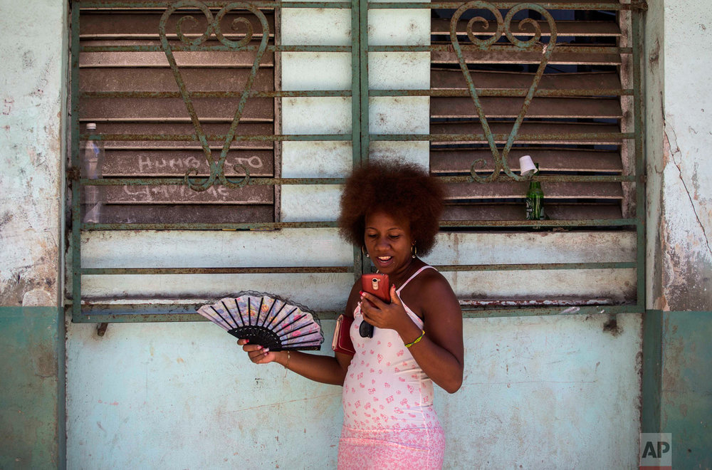 A woman uses her smartphone to surf the internet in Havana, Cuba, Aug. 22, 2018. The state telecommunications company launched on Wednesday the latest, and most extensive, of a recent series of test runs of a mobile network that would give citizens greater access to the internet than has existed before on the island. (AP Photo/Desmond Boylan)