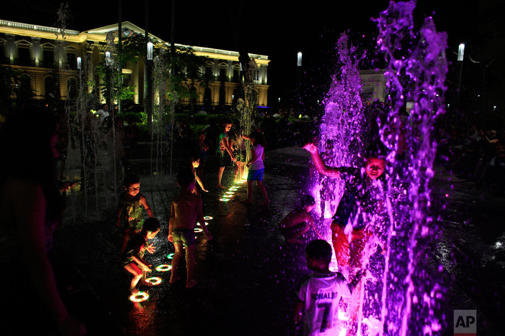 Children run through an illuminated fountain near the National Palace in San Salvador, El Salvador, Aug. 19, 2018. Earlier this year, the capital opened its newly-renovated downtown heart, with a pedestrian zone linking several updated squares in the capital's historic center. Where public transit buses and market stalls once clogged the streets, local residents enticed by both new amenities and greater security now stroll, play, or watch street concerts. (AP Photo/Rebecca Blackwell)