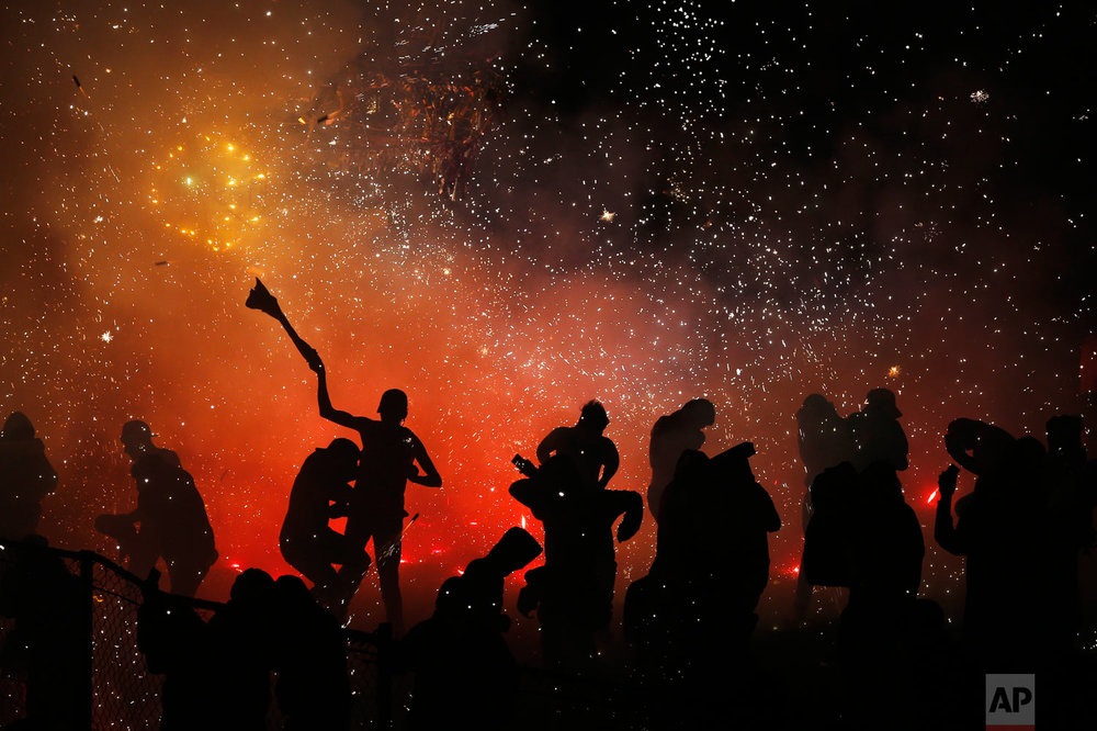 In this July 30, 2018 photo published in August, revelers play in and around a huge burning papier mache bull full of exploding fireworks, in the Santiago Teyuhalco neighborhood of Tultepec, Mexico. Last year there were 40 fireworks accidents in the State of Mexico, where Tultepec is located, that claimed 24 lives and injured more than 100, according to the governmental Mexican Institute of Pyrotechnics; through July 5 of this year, there have been 16 accidents with 40 dead and more than 70 hurt. (AP Photo/Marco Ugarte)