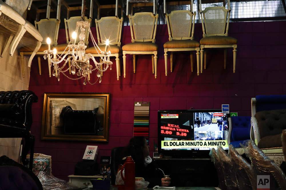 A woman watches news regarding U.S. dollar rates in Buenos Aires, Argentina, Aug. 30, 2018. Argentina's Central Bank on Thursday increased its benchmark interest rate to 60 percent — the world's highest — in an effort to halt a sharp slide in the value of the peso, which plunged to a new record low. (AP Photo/Natacha Pisarenko)