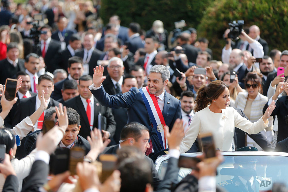 """Paraguay's new President Mario Abdo Benitez rides in an open top car with his wife Silvana Lopez, after his inauguration ceremony at """"Lopez Palace"""" in Asuncion, Paraguay, Aug. 15, 2018. (AP Photo/Jorge Saenz)"""