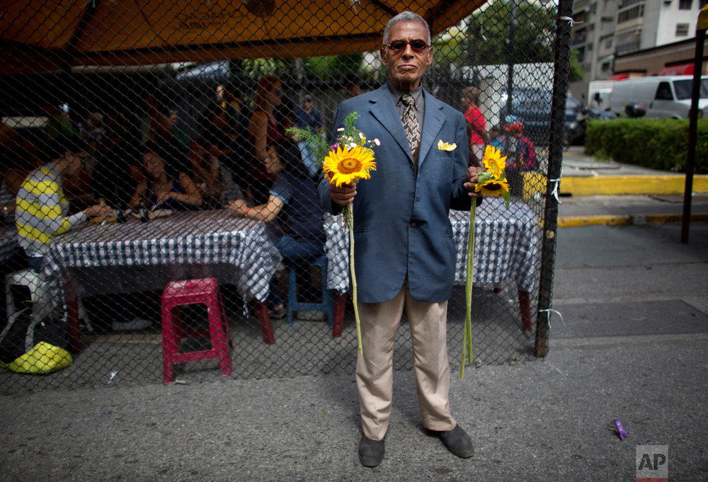 Humberto Castillo, 72, offers sun flowers for sale or to exchange them for food, at a street market in Caracas, Venezuela, Aug. 18, 2018. Venezuelan President Nicolas Maduro raised wages for the fifth time this year while saying he's looking to establish a single exchange rate tied to the nation's fledgling cryptocurrency. (AP Photo/Ariana Cubillos)