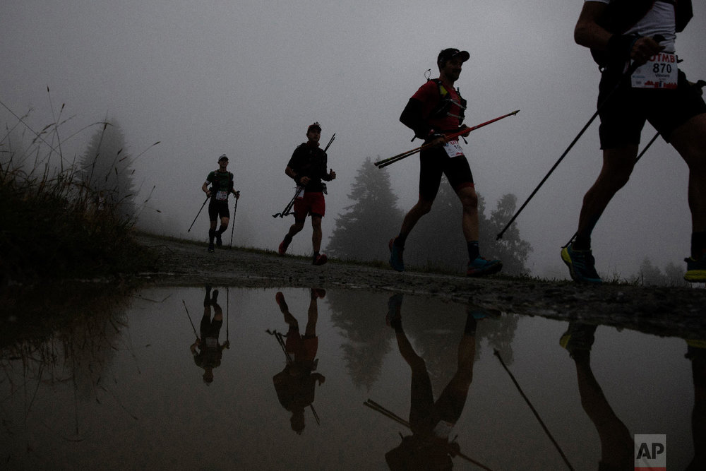 Competitors run along the Voza path as they compete in the 170km Ultra-Trail of Mont-Blanc (UTMB) race, in Saint Gervais-les- Bains, French Alps, Aug. 31, 2018. (AP Photo/Laurent Cipriani)