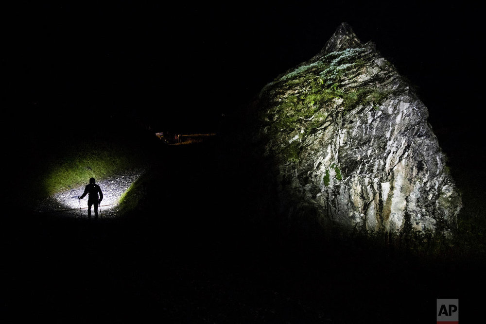A competitor runs in the night on the Balmes path as he competes in the 170km Ultra-Trail of Mont-Blanc (UTMB) race, in Les Contamines Montjoie, French Alps, Aug. 31, 2018.(AP Photo/Laurent Cipriani)