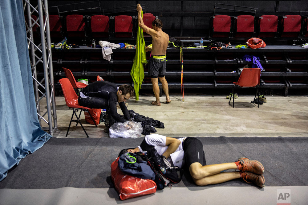Competitors take some rest in the middle of the night at a refreshment post as they compete in the 170km Ultra-Trail of Mont-Blanc (UTMB) race, in Courmayeur, Italy, Sept 1, 2018. (AP Photo/Laurent Cipriani)
