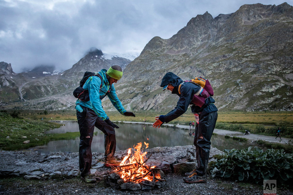 Competitors warm themselves up in front of a fire at the Combal lake as they compete in the 170km Ultra-Trail of Mont-Blanc (UTMB) race, in Courmayeur, Italy, Sept 1, 2018. (AP Photo/Laurent Cipriani)