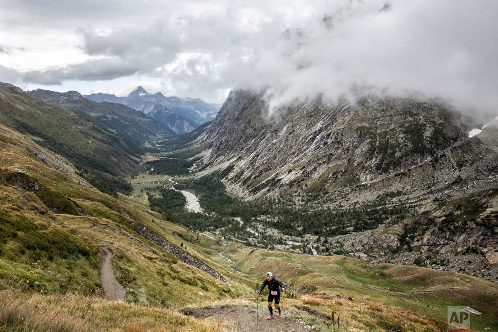 A competitor runs up the Grand Col Ferret as he competes in the 170km Ultra-Trail of Mont-Blanc (UTMB) race, near Courmayeur, Italy, Saturday, Sept 1, 2018. (AP Photo/Laurent Cipriani)