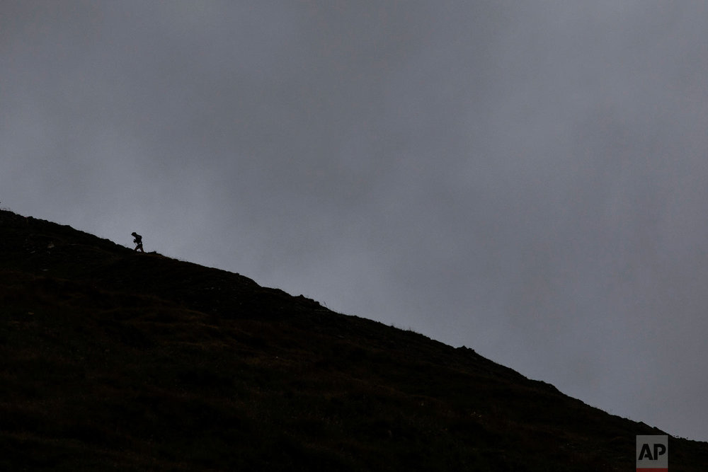 A competitor runs up the Grand Col Ferret as he competes in the 170km Ultra-Trail of Mont-Blanc (UTMB) race, near Courmayeur, Italy, Sept 1, 2018. (AP Photo/Laurent Cipriani)