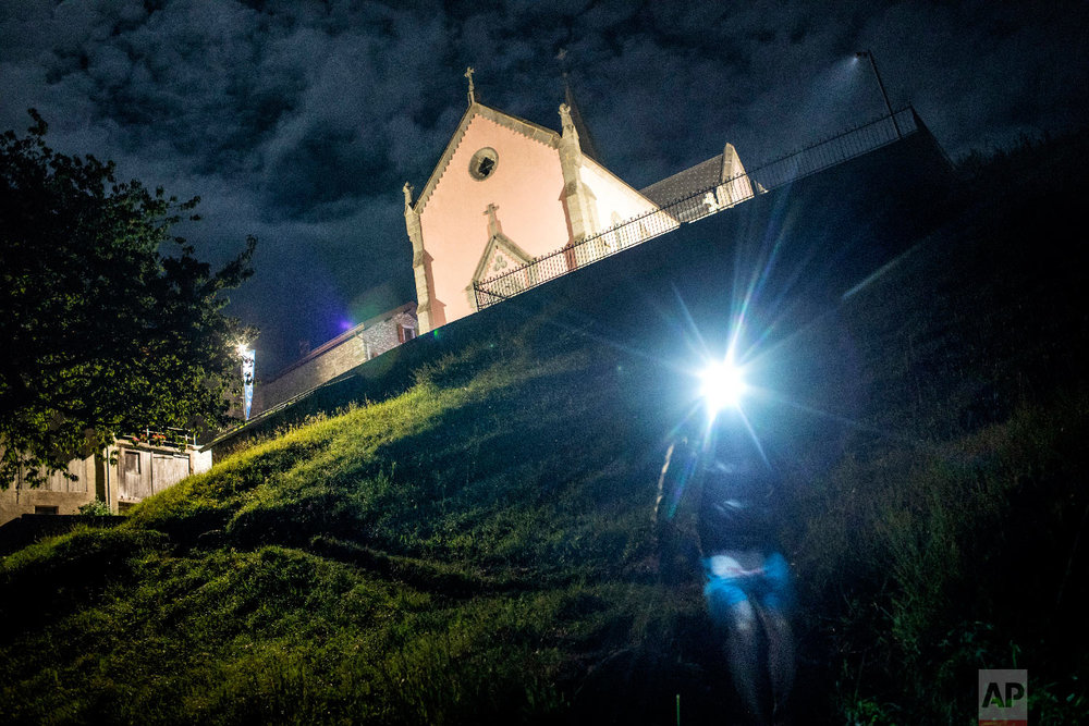 A competitor runs in the night in Trient, Switzerland, as he competes in the 170km Ultra-Trail of Mont-Blanc (UTMB) race, Sept 2, 2018. (AP Photo/Laurent Cipriani)
