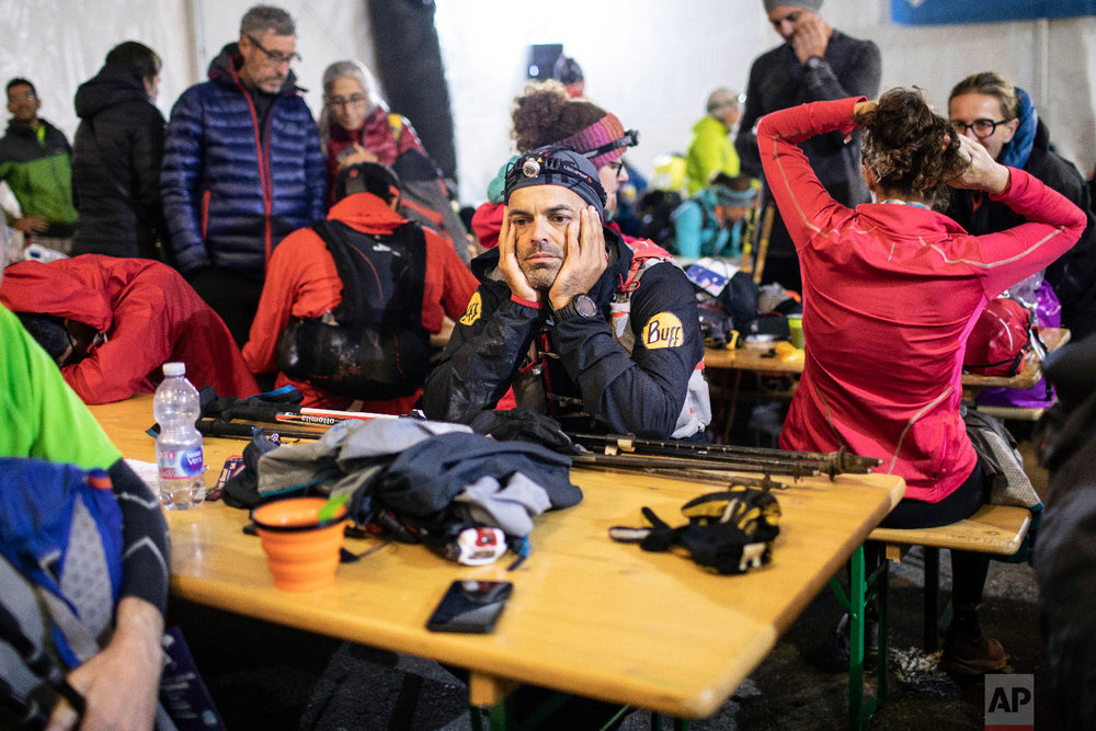 Competitors take some rest in the night at a refreshment post in Trient, Switzerland, as they compete in the 170km Ultra-Trail of Mont-Blanc (UTMB) race, Sept 2, 2018. (AP Photo/Laurent Cipriani)