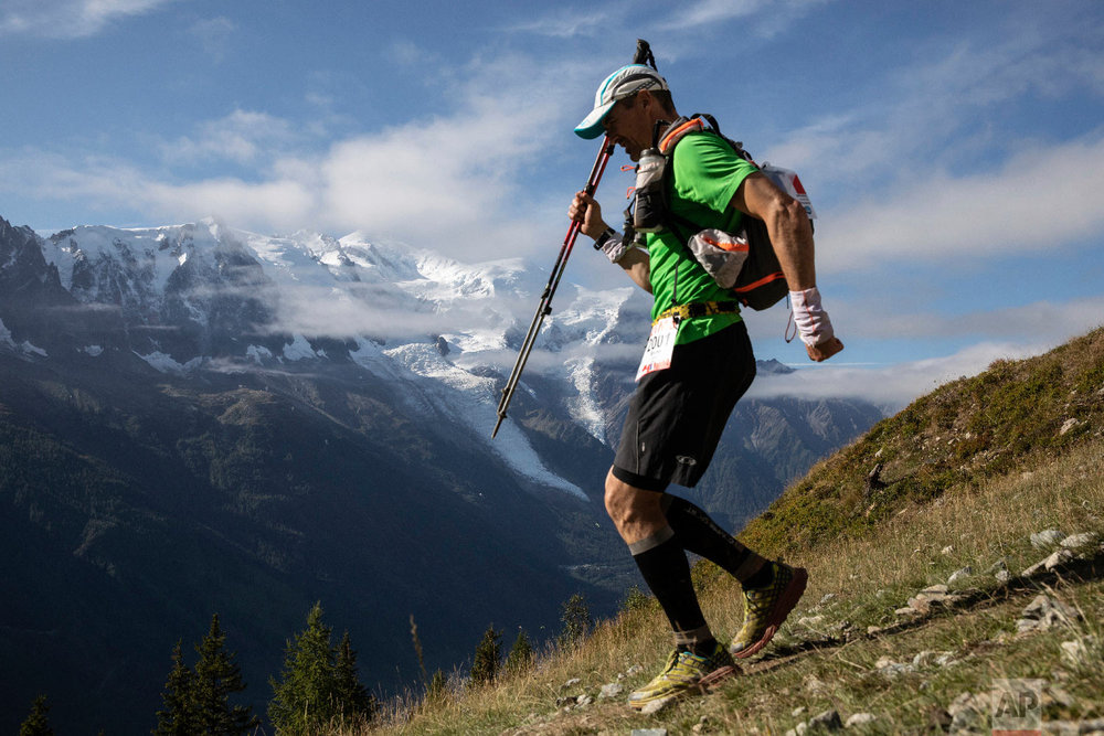 A competitor walks past Mont Blanc in background at La Flegere path as he competes in the 170km Ultra-Trail of Mont-Blanc (UTMB) race, near Chamonix, French Alps, Sept 2, 2018.(AP Photo/Laurent Cipriani)