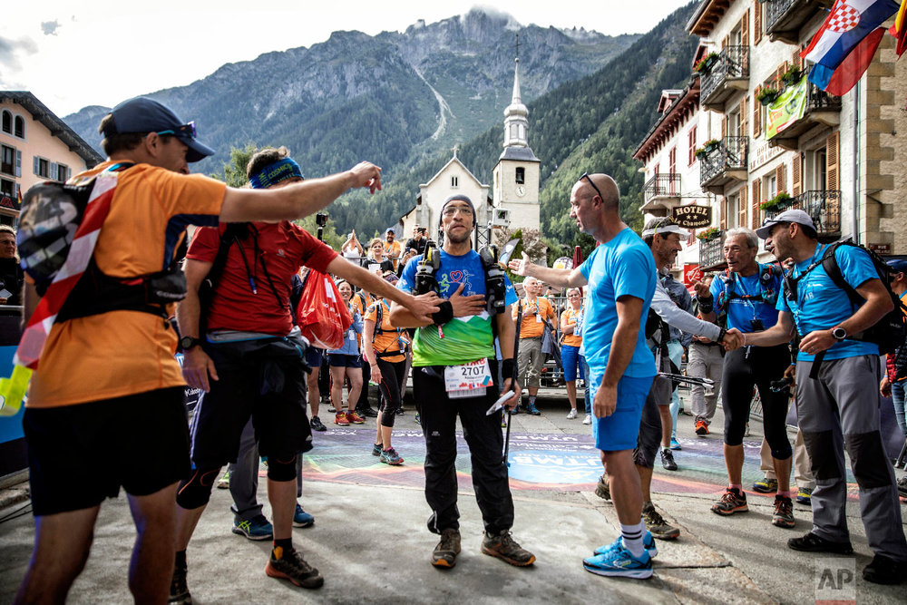 Abdennour Benmammar of France, the last finisher, is congratulated after crossing the finish line at the end of the 170km Ultra-Trail of Mont-Blanc (UTMB) race, near Chamonix, French Alps, Sept 2, 2018. (AP Photo/Laurent Cipriani)