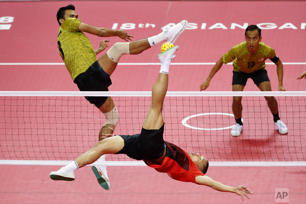 Indonesia's Nofrizal Nofrizal, back, kicks a ball against Malaysia's Farhan Adam during men's regu sepak takraw final match between Indonesia and Malaysia at the 18th Asian Games in Palembang, Indonesia, Tuesday, Aug. 28, 2018. (AP Photo/Vincent Thian)