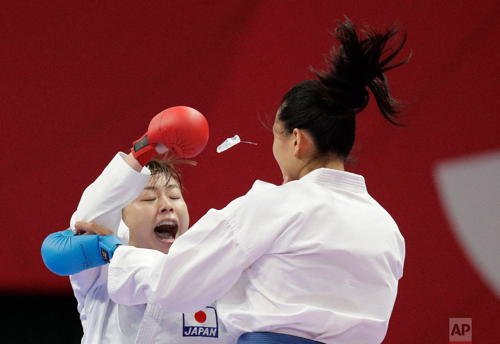 The mouthpiece of China's Mengmeng Gao, right, flies out during her fight with Japan's Ayumi Uekusa during their women's 68kg kumite karate at the 18th Asian Games in Jakarta, Indonesia, Saturday, Aug. 25, 2018. Uekusa won the gold. (AP Photo/Aaron Favila)