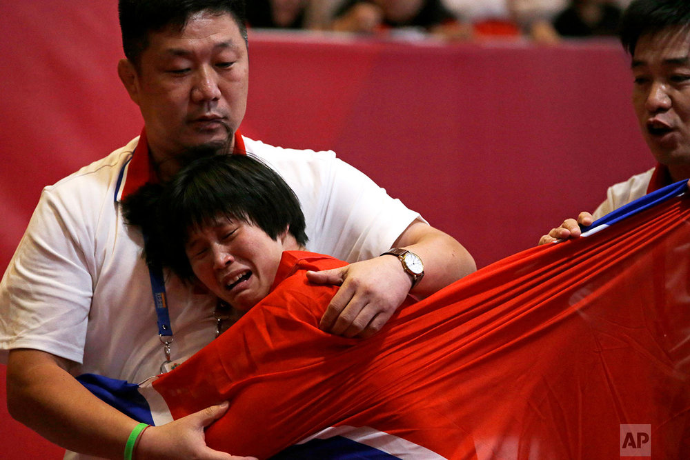 Pak long Ming of North Korea reacts as she win over Zhuldyz Eshimova of Kazakstan  during woman's freestyle 53 kg wrestling at the 18th Asian Games in Jakarta, Indonesia, Monday, Aug. 20, 2018. (AP Photo/Firdia Lisnawati)