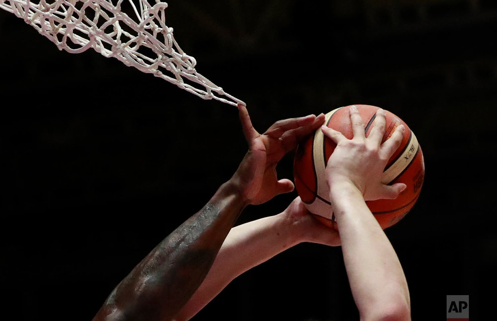 The finger of South Korea's Ricardo Ratliffe is caught in the net as he blocks a shot by Taiwan's Chen Kuanchuan during their men's basketball bronze medal match at the 18th Asian Games in Jakarta, Indonesia, Saturday, Sept. 1, 2018. (AP Photo/Dita Alangkara)