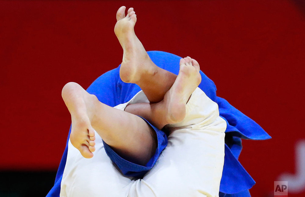 The leg of China's Wang Yan, in blue, is locked by Taiwan's Tsai Jiawen's during their women's +78 kg judo bronze medal match at the 18th Asian Games in Jakarta, Indonesia, Friday, Aug. 31, 2018. (AP Photo/Dita Alangkara)