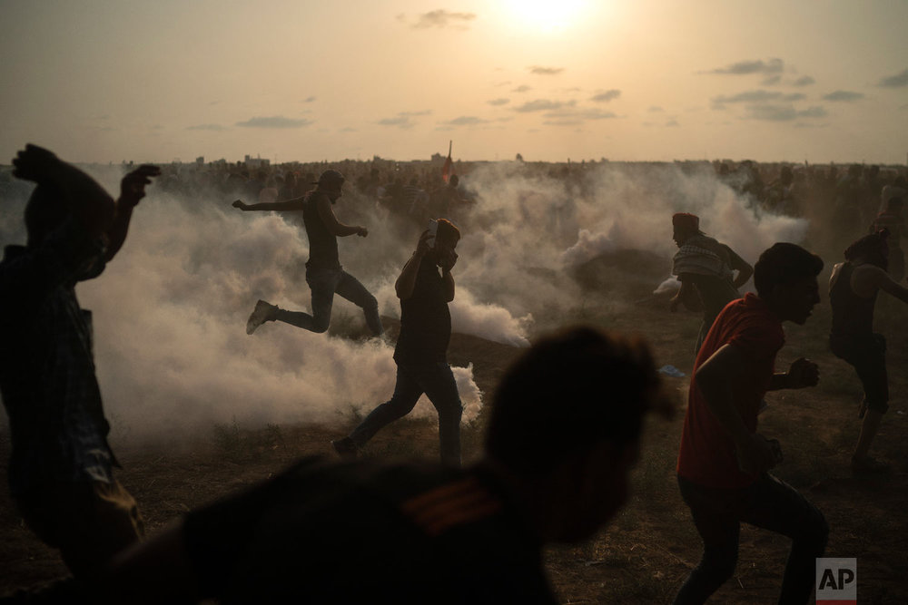 Palestinian protesters kick back teargas fired by Israeli troops during a protest at the Gaza Strip's border with Israel, east of Gaza City, Friday, Aug. 31, 2018. (AP Photo/Felipe Dana)