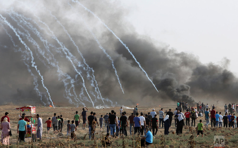 Protesters walk toward the fence where the Israeli troops fire teargas while others burn tires near the fence of the Gaza Strip border with Israel, during a protest east of Gaza City, Friday, Aug. 31, 2018. (AP Photo/Adel Hana)