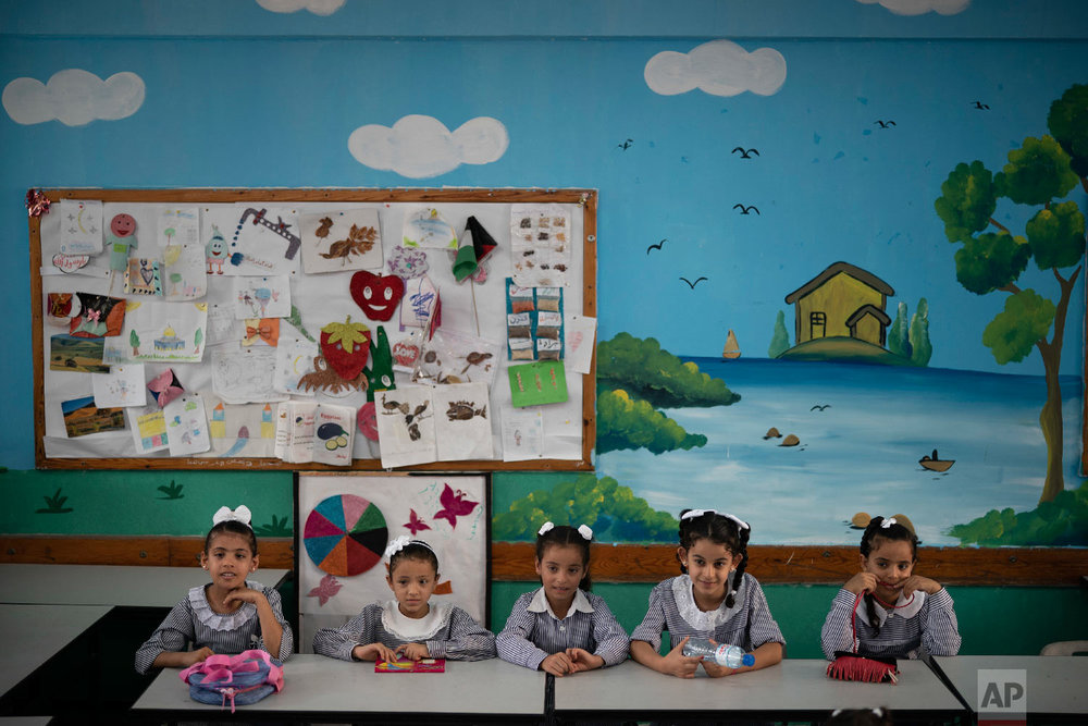 Girls sit inside a classroom at an UNRWA school during the first day of a new school year in Gaza City, Wednesday, Aug. 29, 2018. Hundreds of thousands of Palestinian children are starting their school year in the Gaza Strip amid a major budget crunch for the United Nations agency that funds many schools. (AP Photo/Felipe Dana)