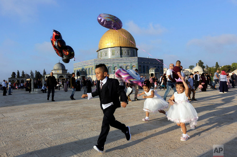 Palestinian children hold balloons on the first day of Eid al-Adha near the Dome of the Rock Mosque in the Al Aqsa Mosque compound in Jerusalem's old city, Tuesday, Aug. 21, 2018. (AP Photo/Mahmoud Illean)