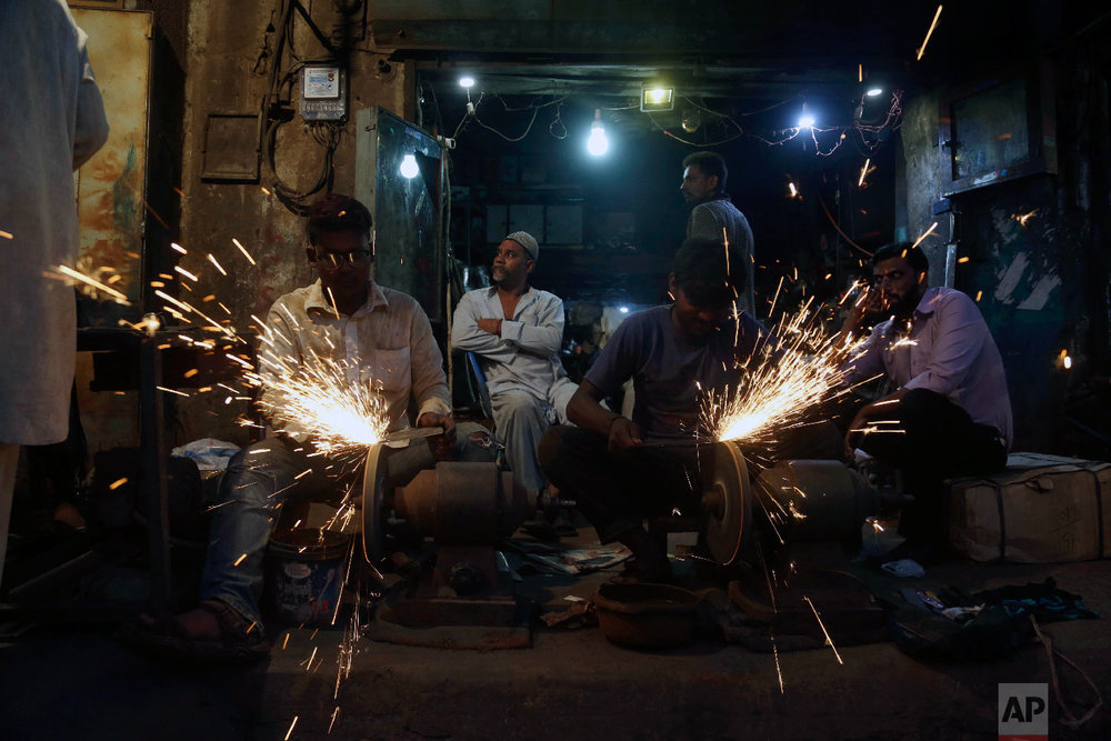 People get their knives sharpened for the upcoming Muslim festival Eid al-Adha in Karachi, Pakistan, Monday, Aug. 20, 2018. (AP Photo/Shakil Adil)