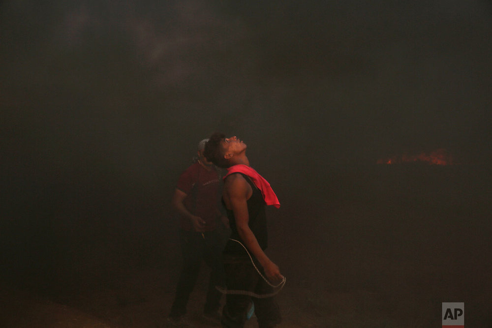 Protesters burn tires near fence of the Gaza Strip border with Israel, during a protest east of Gaza City, Friday, Aug. 31, 2018. (AP Photo/Adel Hana)