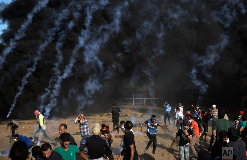 Palestinian protesters escape from teargas fired by Israeli troops during a protest at the Gaza Strip's border with Israel, Friday, Aug.10, 2018. (AP Photo/Khalil Hamra)