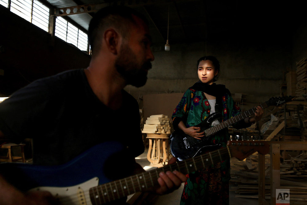 Afghan musicians Hakim Ebrahimi, left, and Soraya Hosseini, members of the Arikayn rock band, play music at a furniture workshop on the outskirts of Tehran, Iran on July 26, 2018. Like others in Iran's vibrant arts scene, Afghan musicians must contend with hard-liners who view Western culture as corrupt and object to women performing in public. (AP Photo/Ebrahim Noroozi)