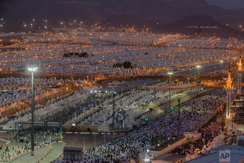 Muslim pilgrims walk back to their tents after casting stones at three huge stone pillars in the symbolic stoning of the devil during the annual hajj pilgrimage, in Mina, outside the holy city of Mecca, Saudi Arabia, Wednesday, Aug. 22, 2018. (AP Photo/Dar Yasin)