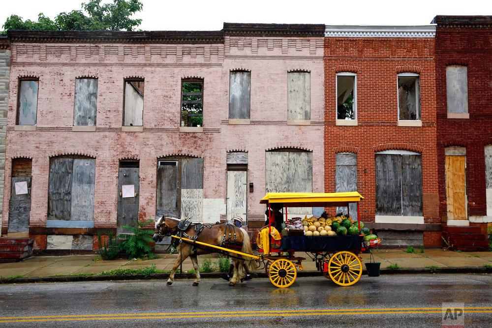 Bilal Yusuf Abdullah leads a horse-drawn arabber cart full of produce past abandoned houses on June 20, 2018, in Baltimore. (AP Photo/Patrick Semansky)