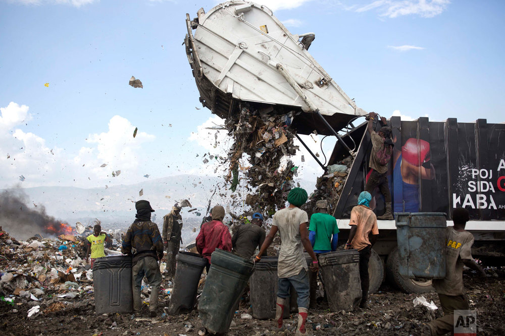 Changlair Aristide, in red shirt at center, waits for a truck to finish dumping its load. Aug. 23, 2018. (AP Photo/Dieu Nalio Chery)