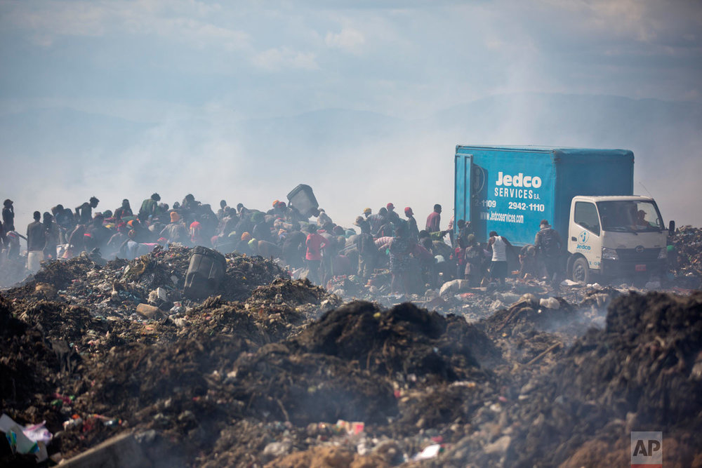 People scavenge behind a truck dumping its load. Aug. 28, 2018. (AP Photo/Dieu Nalio Chery)