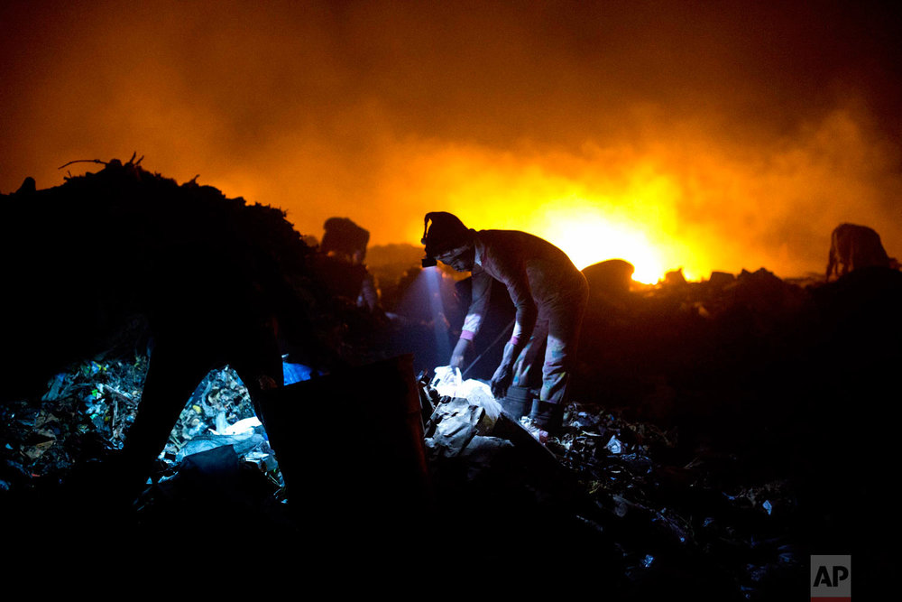 Scavengers use head lamps to continue searching the dump at night. Aug. 30, 2018. (AP Photo/Dieu Nalio Chery)