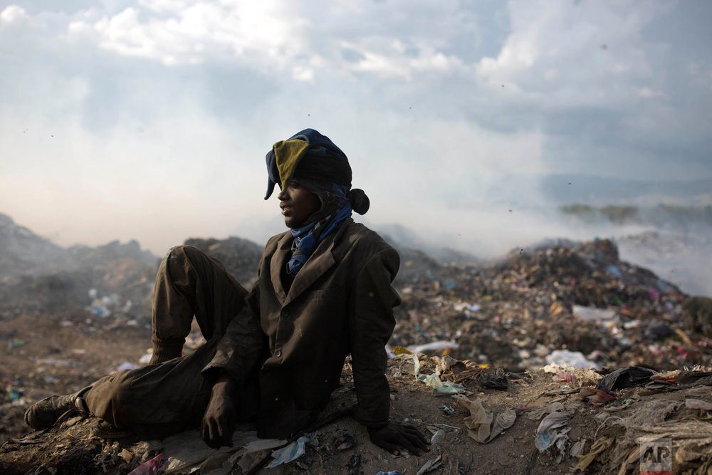 Guerdy Joseph, 24, rests wears a Christmas costume hat he found in the trash, after a work day at the landfill. Joseph has six children, and has been scavenging the dump for the past 10 years. Aug. 30, 2018. (AP Photo/Dieu Nalio Chery)