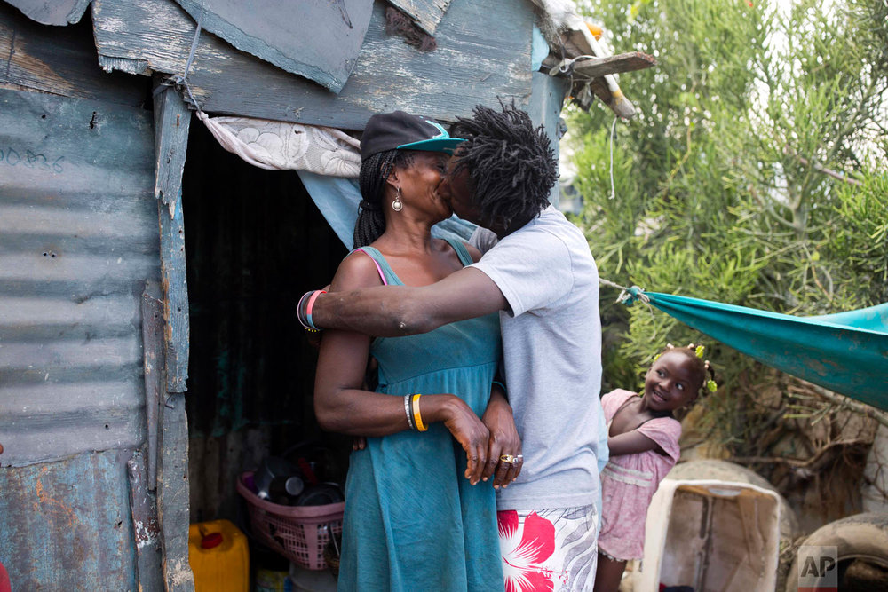 Changlair Aristide kisses his wife Violene Mareus as their daughter Viergeline looks on outside their home.  Mareus cares for their three daughters at home where she sells cigarettes and alcohol. Aug. 25, 2018. (AP Photo/Dieu Nalio Chery)