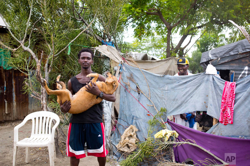 Guerdy Joseph holds his dog outside the home of his friend Changlair Aristide, right, where they live on the edges of the landfill. Aug. 29, 2018. (AP Photo/Dieu Nalio Chery)