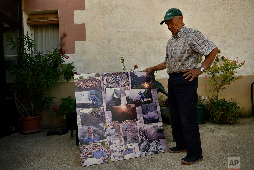 In this Tuesday, Sept.11, 2018 photo, former charcoal worker Emiliano Galdeano, 78, shows some old photographs of himself making traditional charcoal in Viloria, northern Spain.  (AP Photo/Alvaro Barrientos)