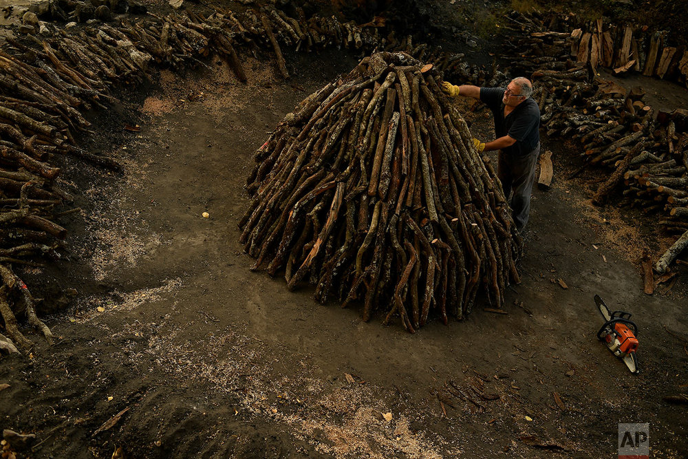 In this Wednesday, Aug. 29, 2018 photo, Jose Mari Nieva, 60, makes a mountain with tree trunks as part of the process to produce traditional charcoal, in the small town of Viloria, northern Spain. (AP Photo/Alvaro Barrientos)