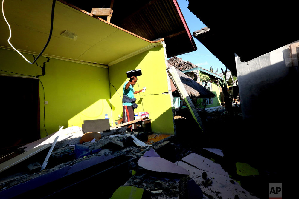 A man salvages items from a home destroyed by a powerful earthquake in North Lombok, Indonesia, Monday, Aug. 6, 2018. (AP Photo/Tatan Syuflana)