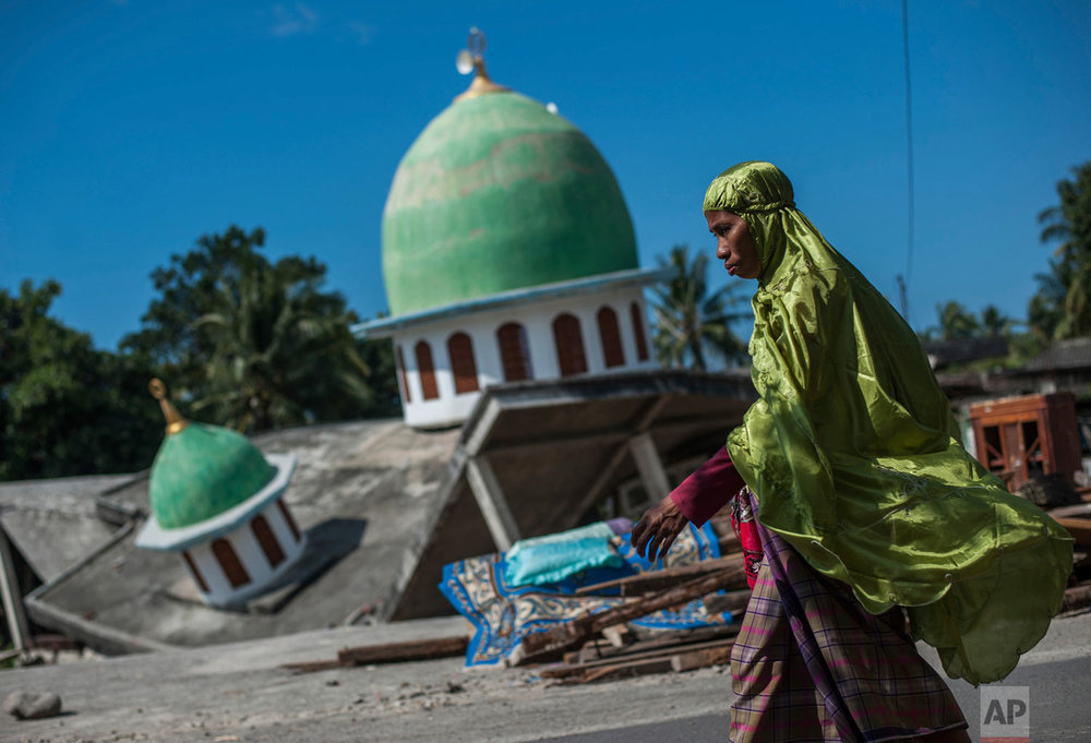 A Muslim woman walks past a mosque which collapsed during a powerful earthquake in Gangga, Lombok Island, Indonesia, Saturday, Aug. 11, 2018. (AP Photo/Fauzy Chaniago)