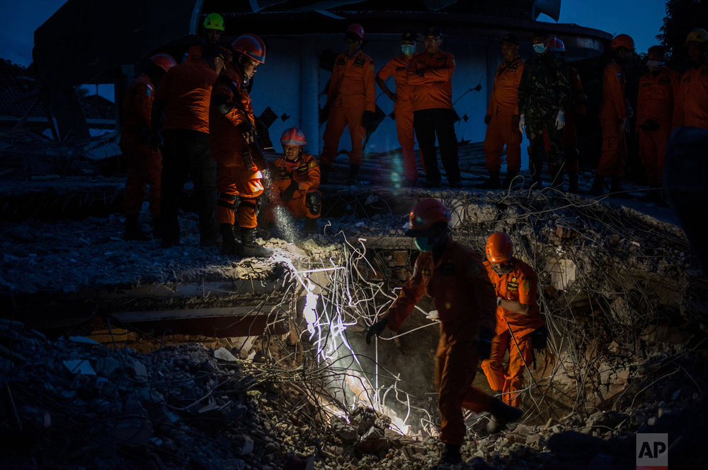 Rescuers search for victims feared buried under the rubble of a building, flattened by an earthquake in Tanjung, Lombok Island, Indonesia, Monday, Aug. 6, 2018. (AP Photo/Fauzy Chaniago)