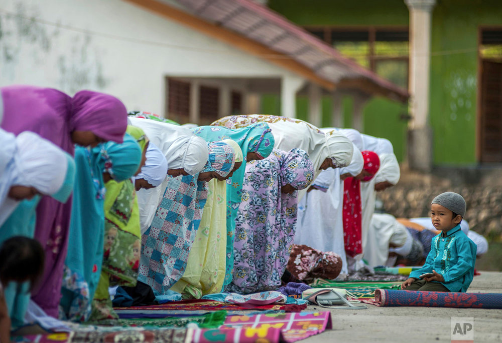People who were affected by an earthquake attend a morning prayer session marking Eid al-Adha in Kokokputek, Lombok Island, Indonesia, Wednesday, Aug. 22, 2018. (AP Photo/Fauzy Chaniago)