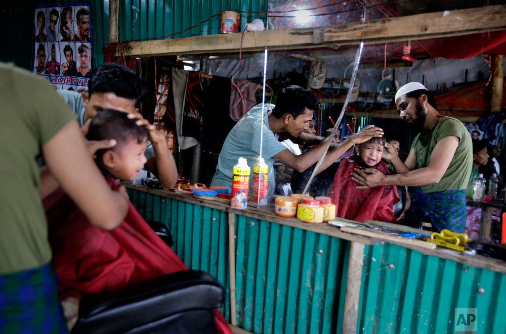 A Rohingya refugee child cries as he gets a hair cut at a makeshift saloon at Balukhali Refugee Camp in Bangladesh, Monday, Aug. 27, 2018. (AP Photo/Altaf Qadri)
