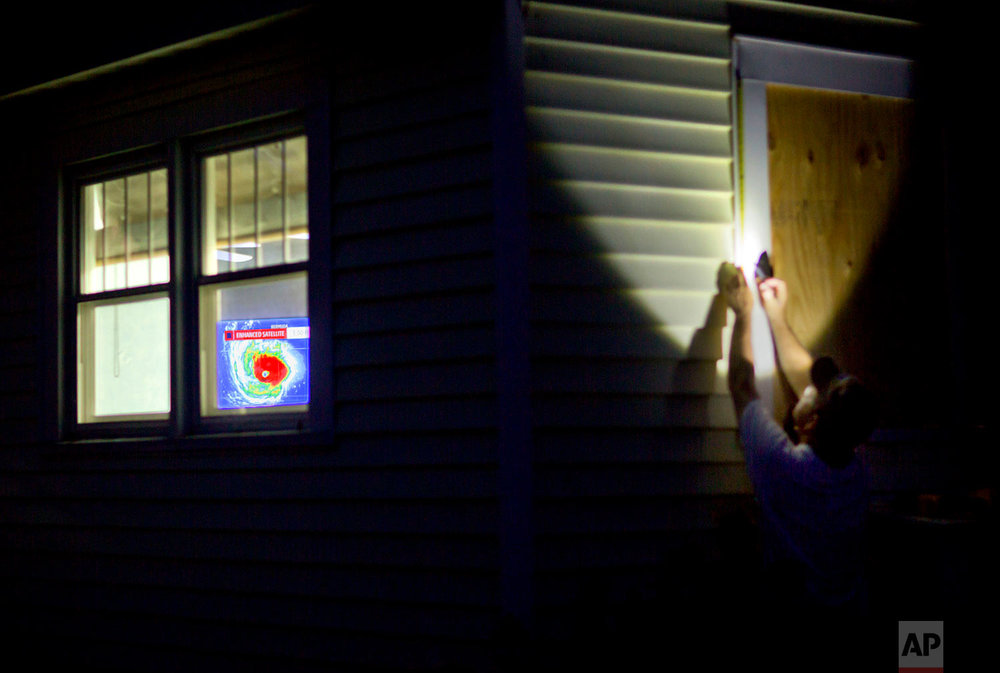 Rob Muller boards up his home as a satellite image of Hurricane Florence is broadcast on a television inside in Morehead City, N.C., Tuesday, Sept. 11, 2018. (AP Photo/David Goldman)