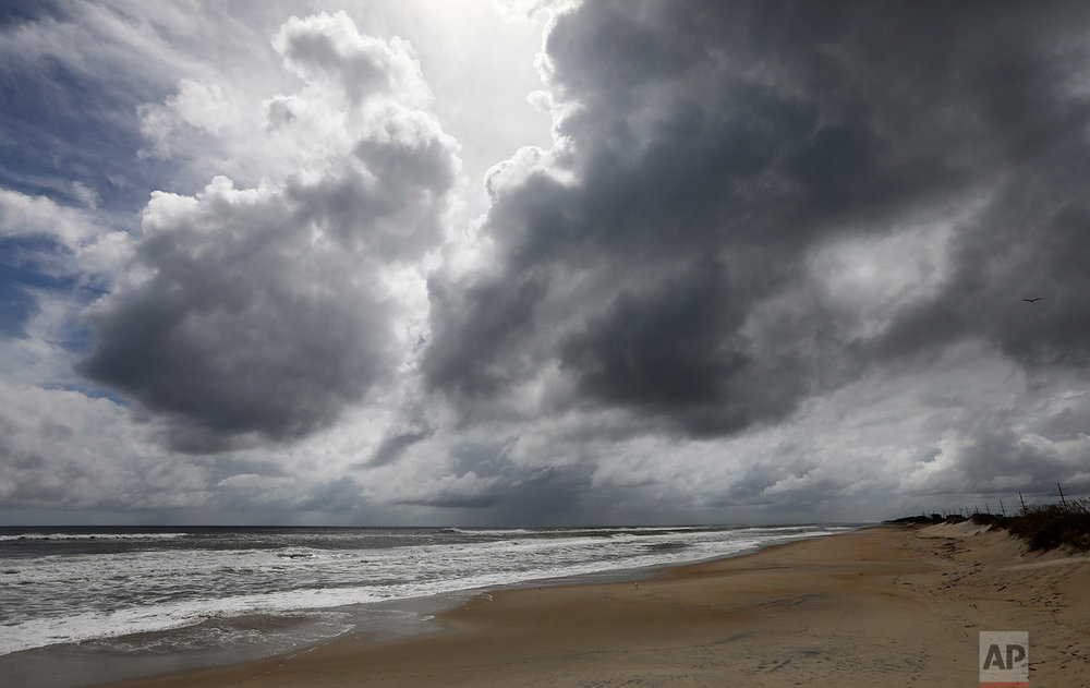 Dark clouds hang off the beach of Hatteras Village at the south end of Hatteras Island, NC., on Wednesday, Sept. 12, 2018. Visitors and many island residents have evacuated because of Hurricane Florence approaching the coast.  (Steve Earley /The Virginian-Pilot via AP)